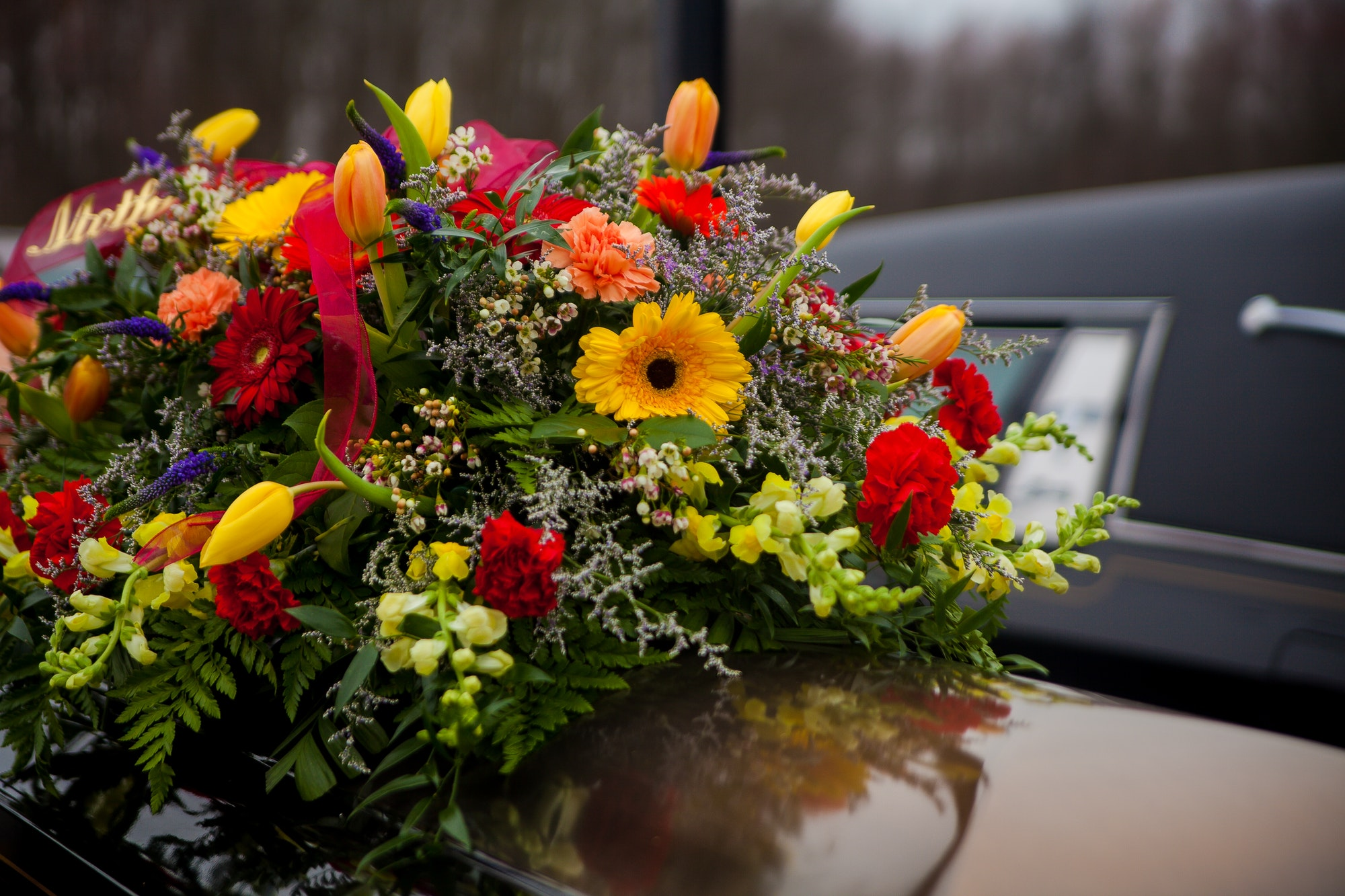 Funeral Casket and flowers next to hearse